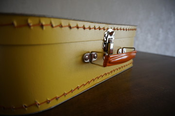 Classic retro suitcase in yellow color on the wooden surface