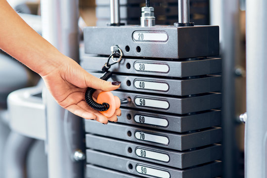 Female hand select weight of gym equipment. Stack of metal weights bodybuilding equipment
