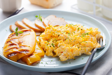 Eggs Scrambled, omelet with grilled bell sweet pepper and hot smocked chicken, ham in a plate on a white background