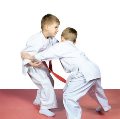 Boys in karategi are training judo techniques