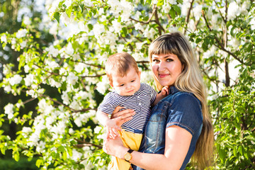 Happy woman and child in beautiful spring blooming garden. Family holiday concept. Mothers day