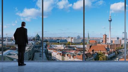 Mann schaut auf Skyline von Berlin