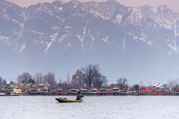 Morning scene of Nigeen lake with the native boat man and the small town behind the mountain range