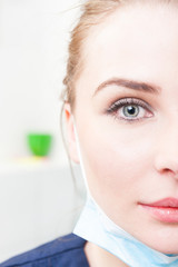 Close-up of half face of female dentist with perfect skin