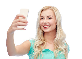 smiling young woman taking selfie with smartphone