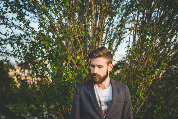 Half length of young handsome bearded man in a park, looking dow