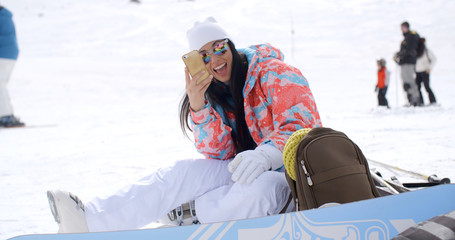 Happy young woman posing for a selfie in the snow as she sits relaxing with her snowboard and gear at a ski resort