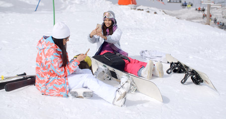 Two attractive young female friends relaxing with their snowboards sitting in the snow in their ski clothes and boots checking out their mobile phones