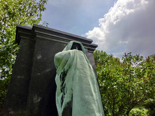 Ominous cloaked figure at cemetery tomb - landscape color photo