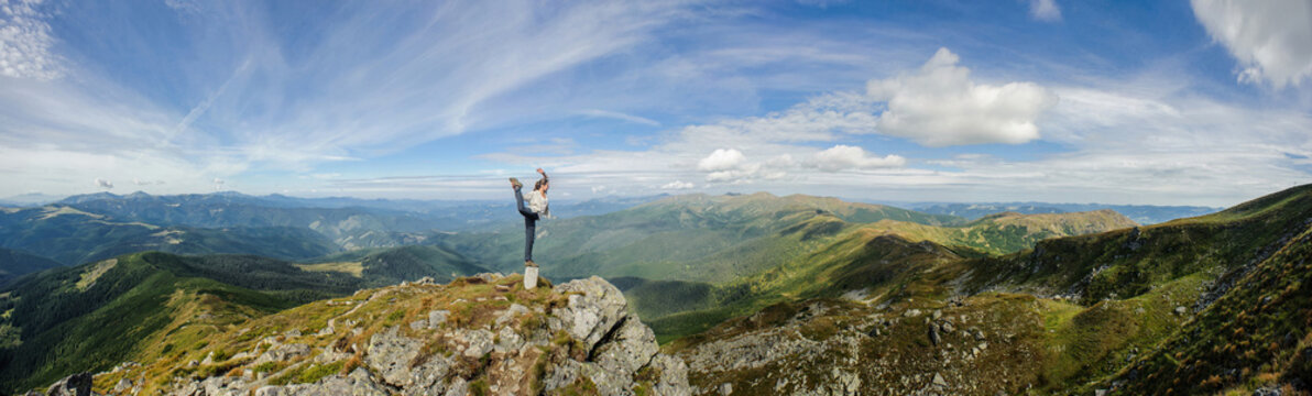 Young woman practices yoga on a mountain top, Carpathian mountains