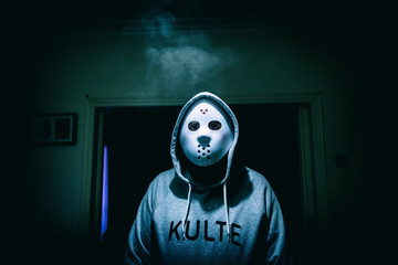 scary man wearing friday and 13th classic white mask in a room