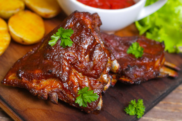Delicious barbecued lamb ribs seasoned with a spicy basting sauce and served with chopped fresh herbs and potatoes on an old rustic wooden chopping board in a country kitchen