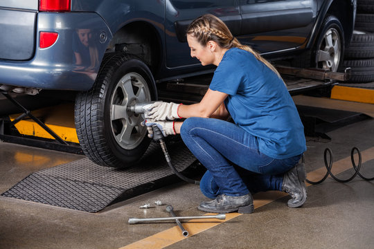 Female Mechanic Fixing Car Tire With Pneumatic Wrench