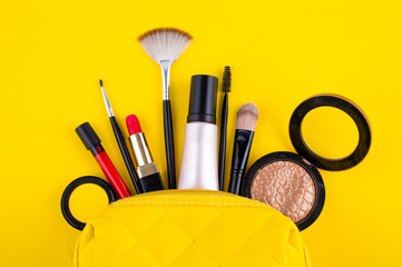 bag with lipstick shades of makeup brushes on a yellow background