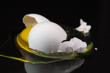 broken organic white egg on black background