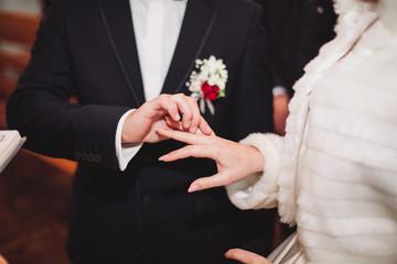 Newlyweds dress wedding ring in the church