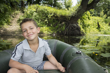 In the summer on the river a little boy sitting in a rubber boat