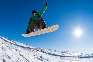 Snowboarder jumping against blue sky Wall mural