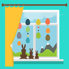 Easter window with garlands of colored Easter eggs. Set of chocolate rabbits on the windowsill.