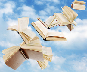 Flying books on cloudy sky background