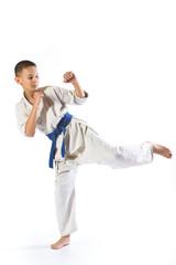 boy in kimono during training karate exercises on  white background