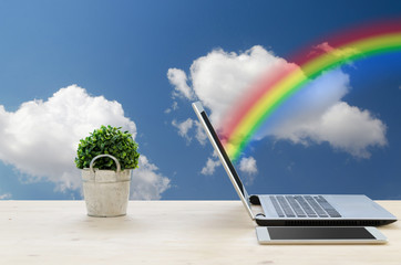 Office Desk with Rainbow above screen a Notebook and tablet.