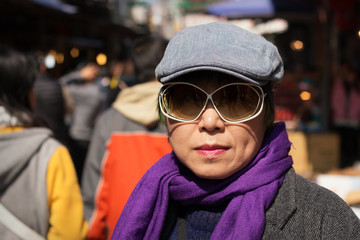 Cool, fashionable mature woman of Chinese ethnicity wearing hat and sunglasses
