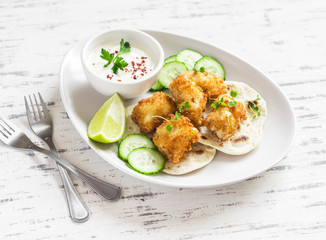 Crispy fried fish on a homemade tortilla on a light wooden background
