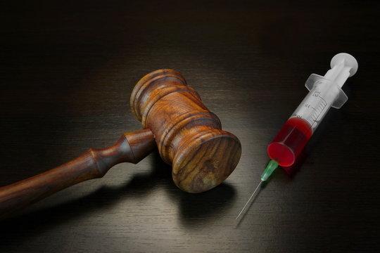 Judges Gavel And Medical Injection Syringe On Black Wooden Backg
