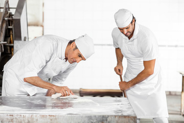 Baker Cleaning Table While Colleague Using Mop