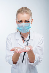 Attractive young blonde female doctor in blue mask with pills on open palms