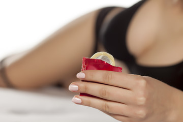 unknown sexy lady lying on a bed and holding a condom