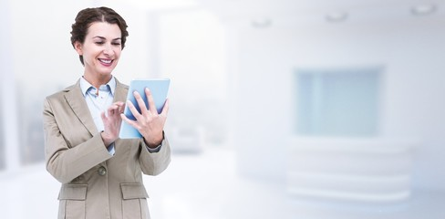Composite image of smiling businesswoman using tablet computer