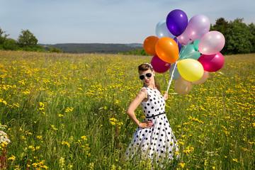 Hübsche Frau im Retro Kleid und Luftballons auf einer Wiese