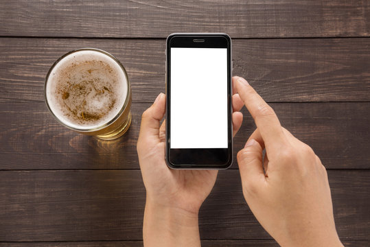 Using smartphone beside of beer in the pub