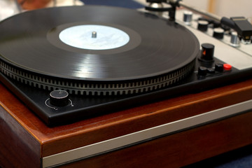 Vintage classic style old school turntable in wooden case playing a vinyl record. Horizontal photo side view from the corner closeup