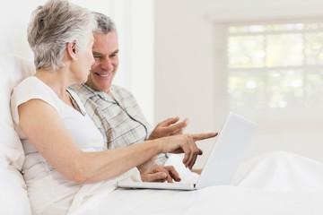 Senior couple using laptop at bed
