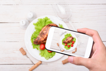 Hands taking photo grilled chicken breast with smartphone.
