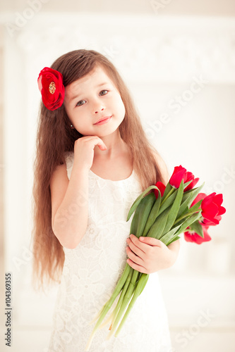 ea78c04ee Smiling baby girl 4-5 year old holding flowers in room over white ...
