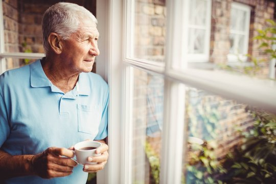 Senior man holding cup and looking out of the window