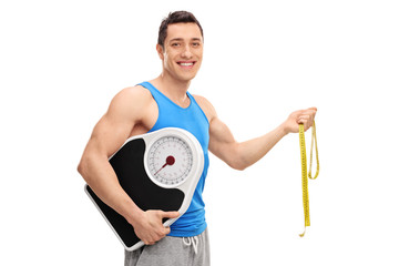 Cheerful athlete holding a weight scale