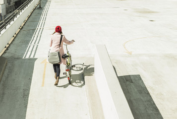 Young woman pushing bicycle on parking level