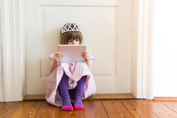 Little girl dressed up as a princess looking at digital tablet