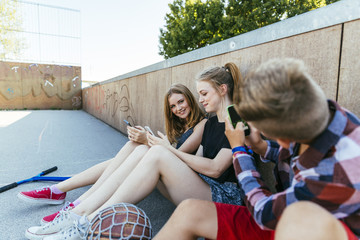 Teenage boy taking cell phone picture of friends outdoors