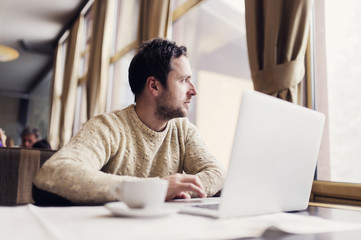 Man with laptop sitting in a coffee shop looking through window