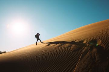 Namibia, Namib Desert, Sossusvlei, Man taking pictures on a dune at sunset
