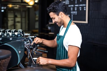 Smiling waiter making cup of coffee