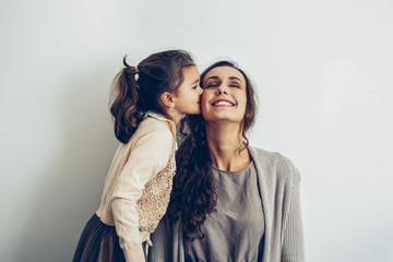 Daughter kissing smiling mother's cheek