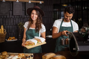 Smiling baristas holding sandwiches and making coffee