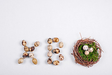 Quail eggs in a nest of twigs with green moss with the words Christ is Risen